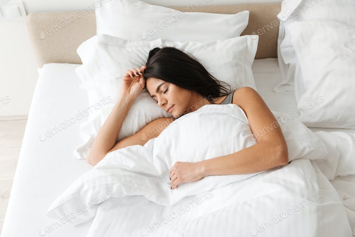 Portrait of peaceful beautiful woman sleeping alone at home in b