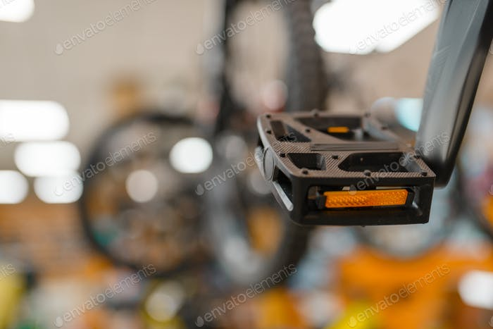 Bicycle in sports shop, focus on pedal, nobody
