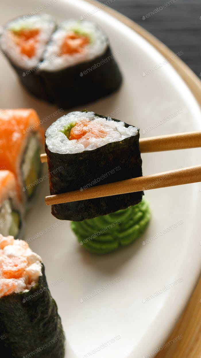 Eating sushi maki in japanese restaurant with wooden sticks
