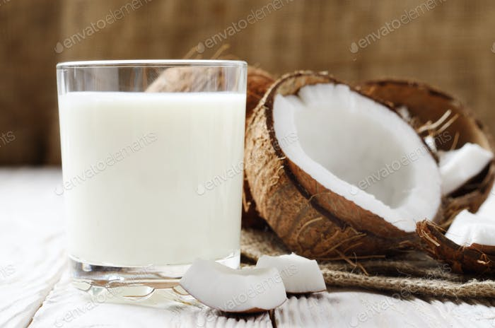 Drinking glass of milk or yogurt on hemp napkin on white wooden