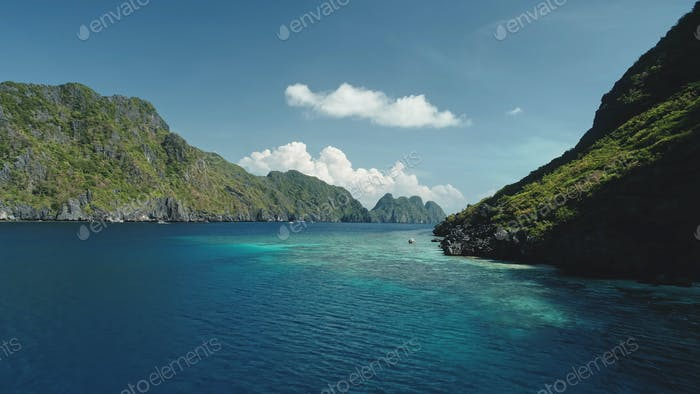 Green cliff shore of sea bay aerial view. Summer nobody seascape at rock ocean coast, Philippines