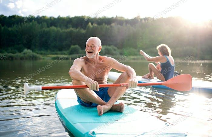 Senior couple paddleboarding on lake in summer