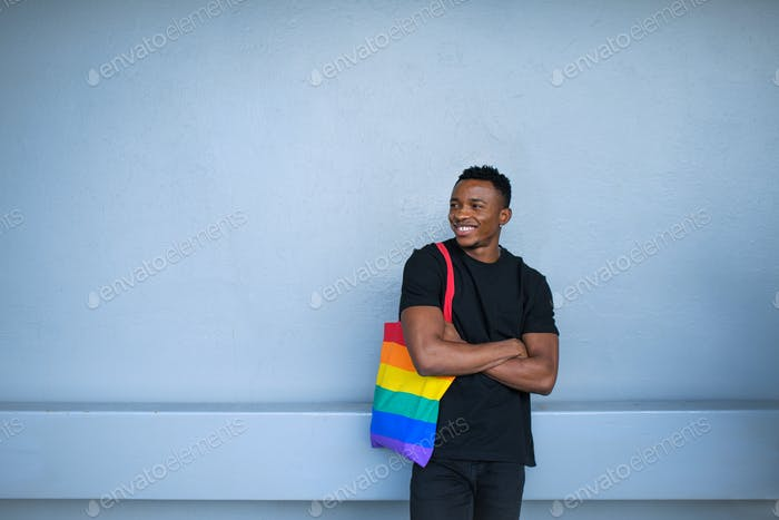 Young black man standing against white wall background, black lives matter concept