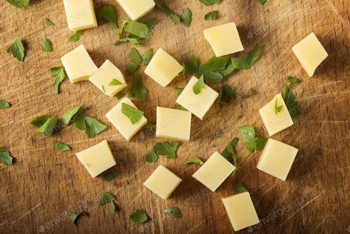 Cubes of yellow cheese with herbs