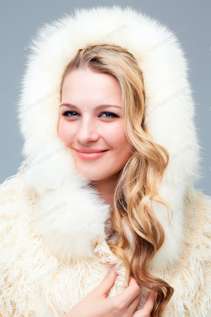 Portrait of blond young woman in fur coat