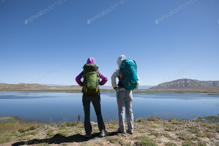 Two bckpackers enjoy the view on high altitude lakeside