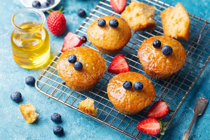 Muffins, Cakes with Fresh Berries and Honey on Cooling Rack.