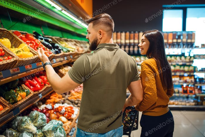 Couple with basket in grocery supermarket together
