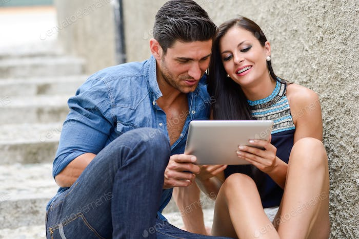 Attractive couple with tablet computer in urban background