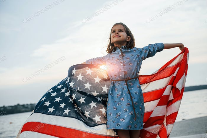 Patriotic female kid with American Flag in hands. Against cloudy sky