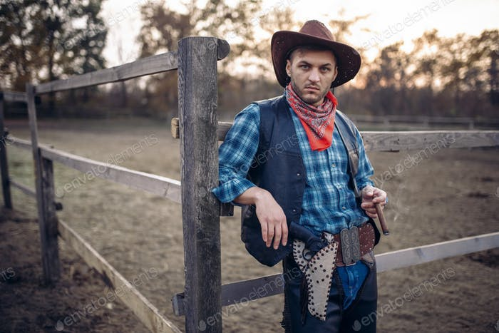 Brutal cowboy poses in the horse corral on ranch