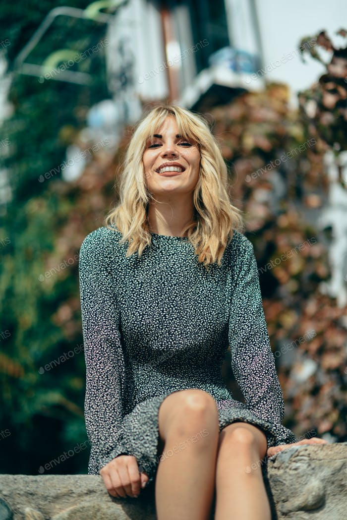 Happy young blond woman sitting on urban autumn background.