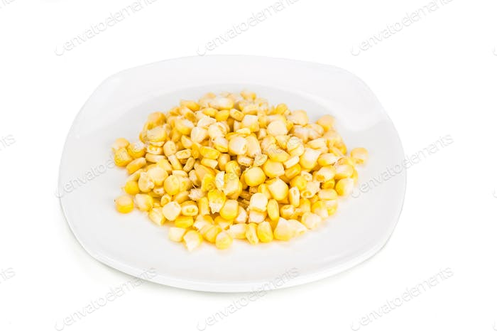 Fresh maize corn kernels on plate against white background