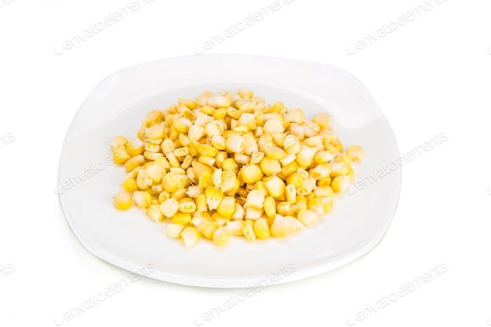 Frische Maiskörner auf Teller vor weißem Hintergrund