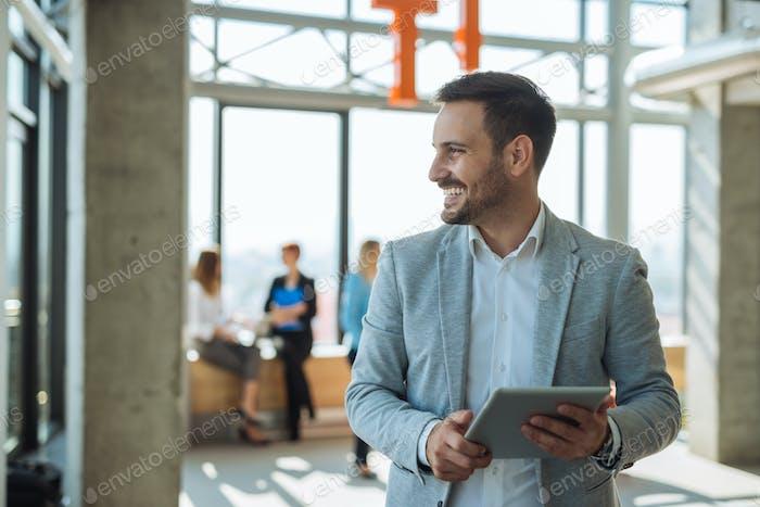Hübscher Geschäftsmann hält ein digitales Tablet