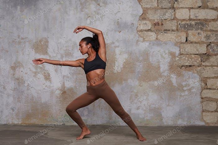 Front full length photo of flexible modern dancer rehearsing in dance studio