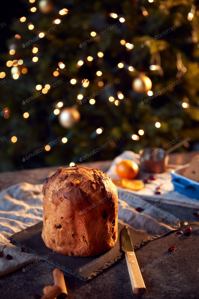 Traditional Christmas Panettone On Table Set For Festive Meal With Tree Lights In Background