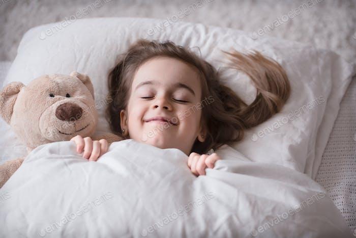 Kleines nettes Mädchen im Bett mit Spielzeug