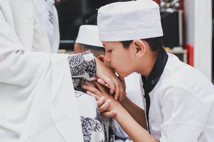 Muslim Boy kissing parents hand on Eid Mubarak