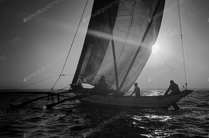 Fishermen on a Catamaran at Sunset