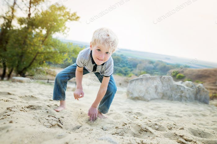 Blond little boy playing on sand beach.