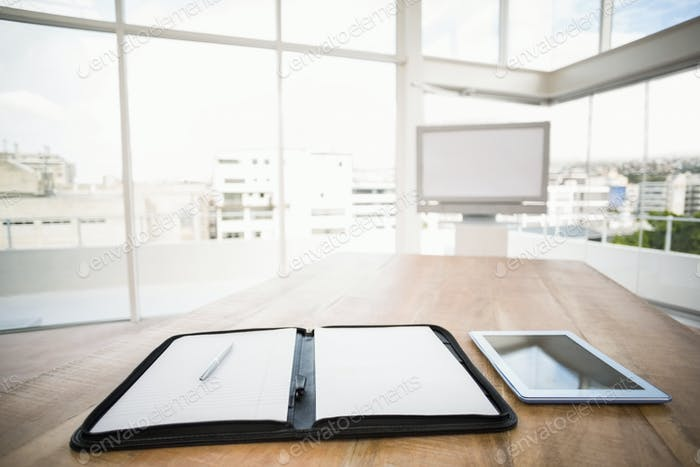 Tablet and planner in front of meeting room in the office