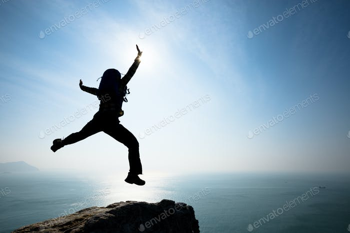 Hipster backpacker jumping on sunrise seaside cliff edge