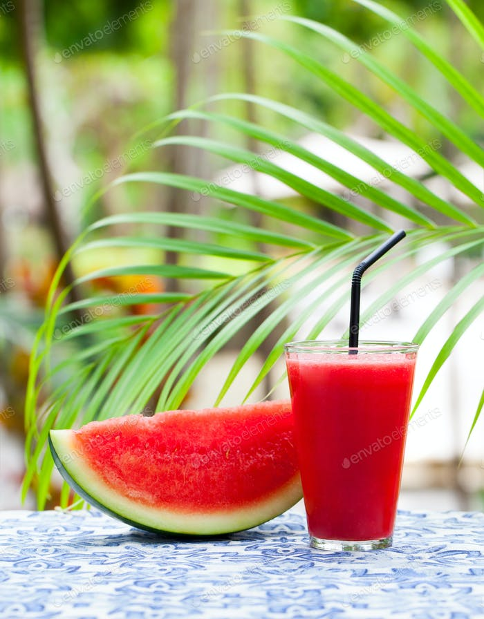 Watermelon Fresh Juice, Smoothie on Tropical Outdoor Background with Palm Leaves. Copy space.