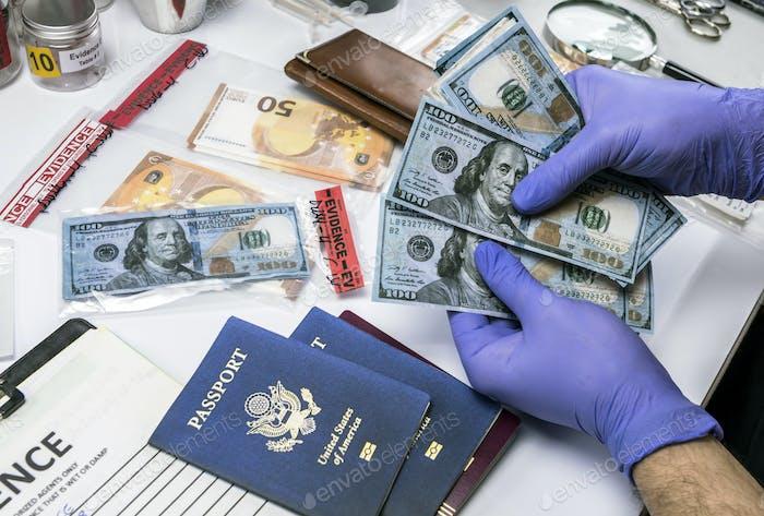 Police scientist checks hundred dollar bills in criminal investigation unit, conceptual image