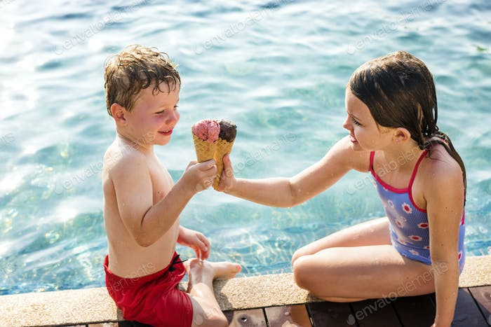 Kids toasting with ice creams at the poolside