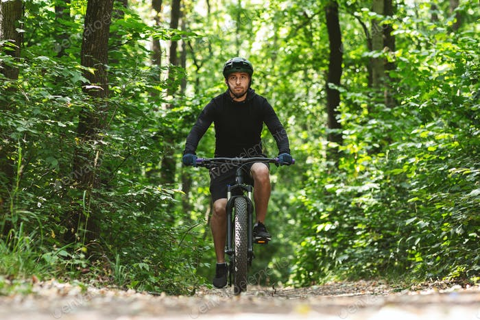 Caucasian man riding bike down the forest trail