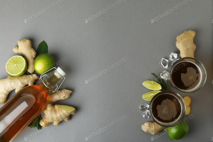 Glasses and bottle of ginger beer and ingredients on gray background