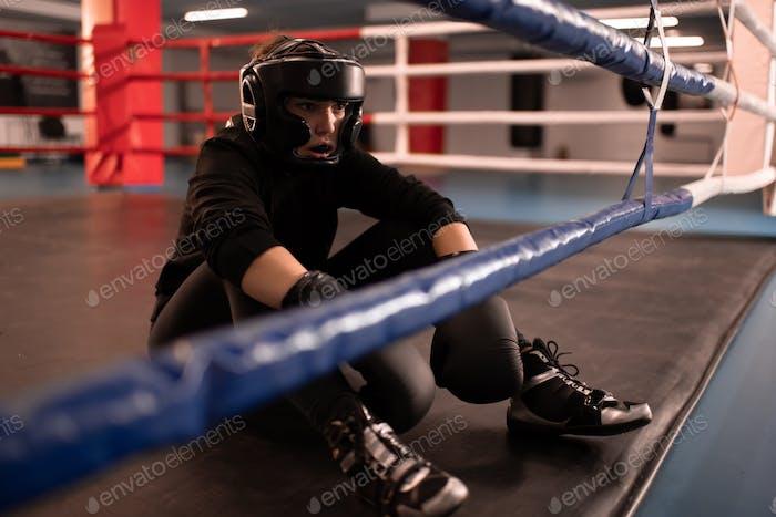 Müde weibliche Boxer ruht nach dem Spiel im Fitnessstudio