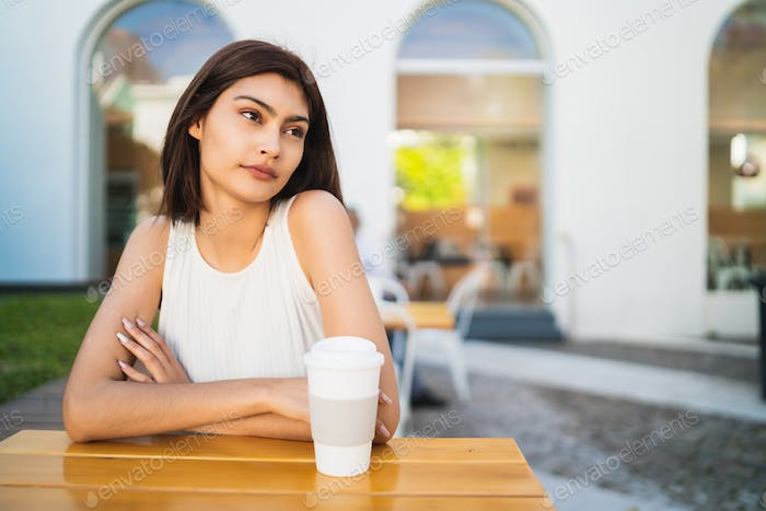 Young woman drinking a cup of coffee at coffee shop.