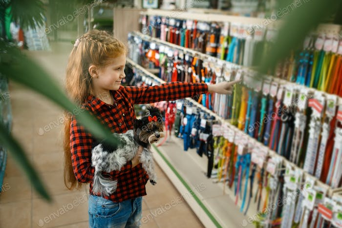 Little girl choosing leash and collar, pet store