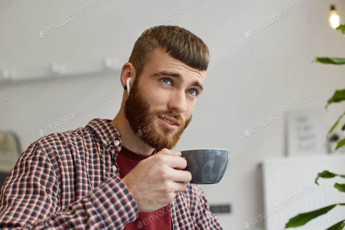 attractive ginger bearded man holding a gray coffee cup