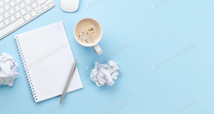 Schreibtisch mit Vorräten, Kaffee und leerem Notizblock