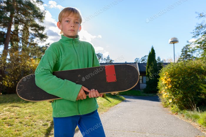 Young handsome boy holding skateboard in the front yard
