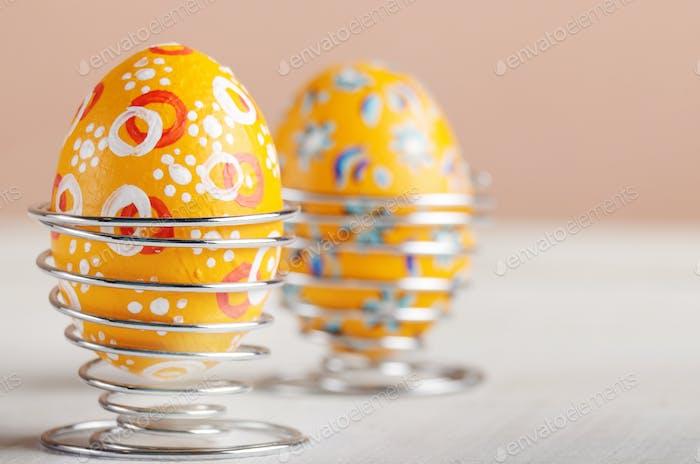 Draht Eierbecher mit bemalten Ostereier auf weißem Tisch