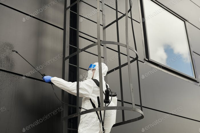 Worker Cleaning Black Facade