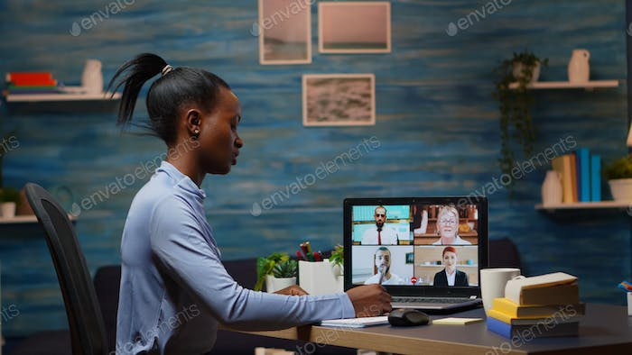 Black freelancer working remotely speaking with coworkers online