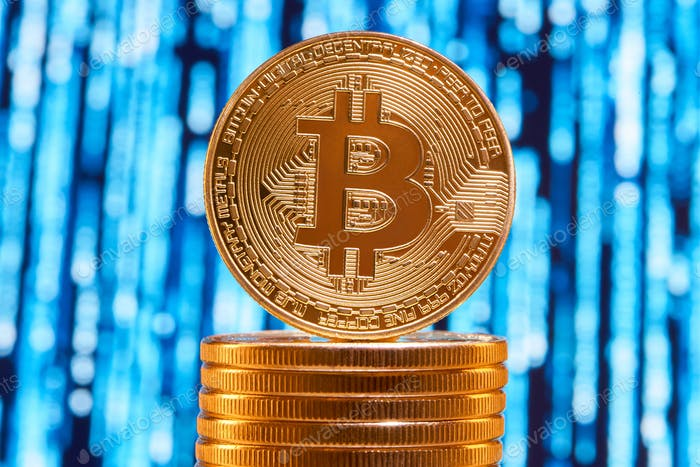 One bitcoin on edge placed on stack of golden bitcoins with blurred blue circuit on background