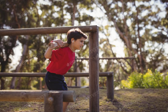 Happy boy exercising with log while listening music during obstacle course