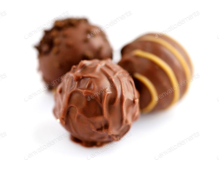 Three candies of milk chocolate on white background. Selective f