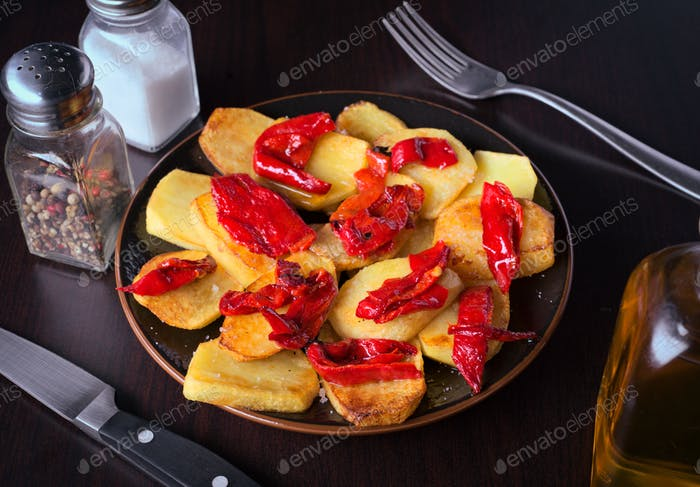 plate of cooked potatoes with peppers on classic wooden background