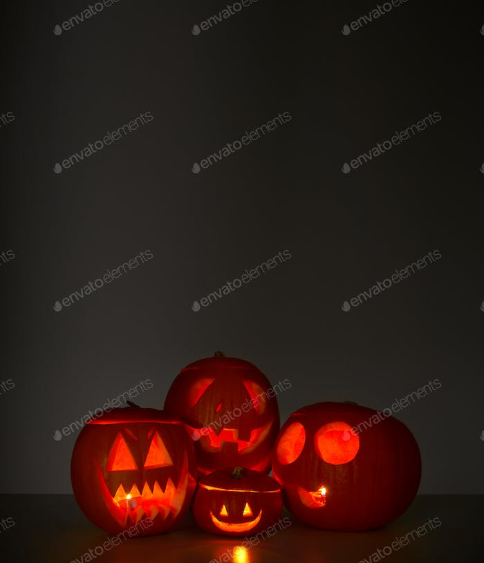 Halloween Still Life Composed Of Carved Pumpkin Jack O'Lanterns Illuminated With Candles