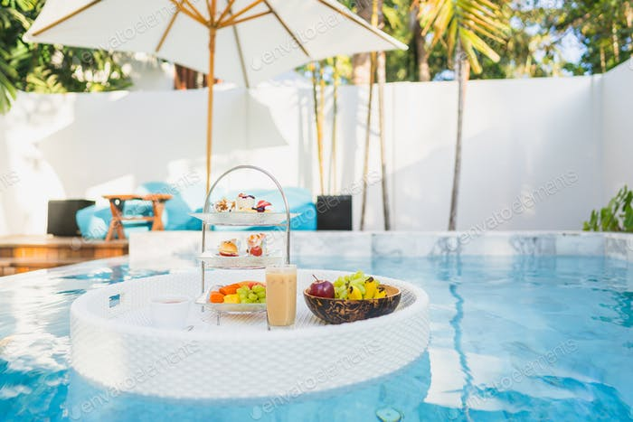 Breakfast and afternoon tea set floating around swimming pool