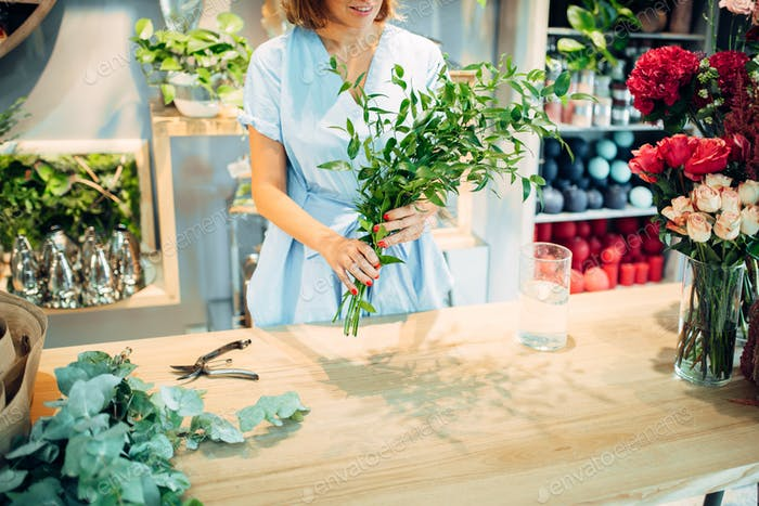 Female florist holds fresh flowers in floral shop