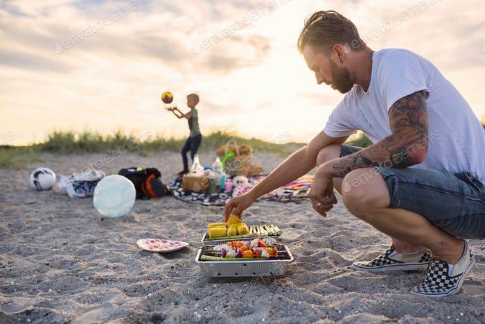 Father and son (4-5) barbecuing on beach