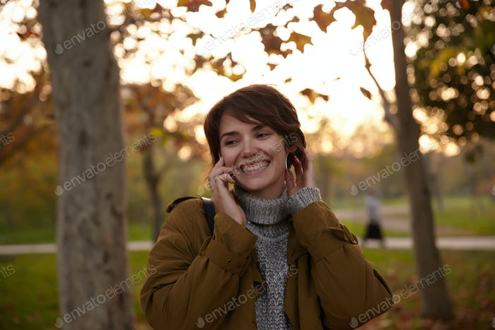 Good looking cheerful young short haired brunette lady with short haircut touching gently